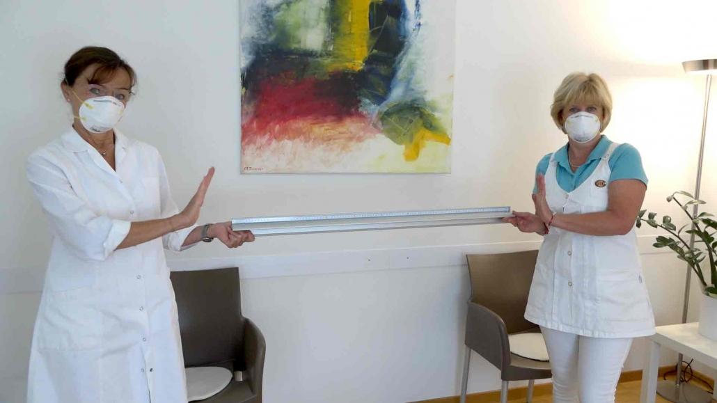 Das Foto zeigt Frau Doktor Astrid Nader mit Ihrer Assistentin im Wartezimmer Ihrer Ordination mit einem Lineal, welches das Abstandhalten veranschaulichen soll.